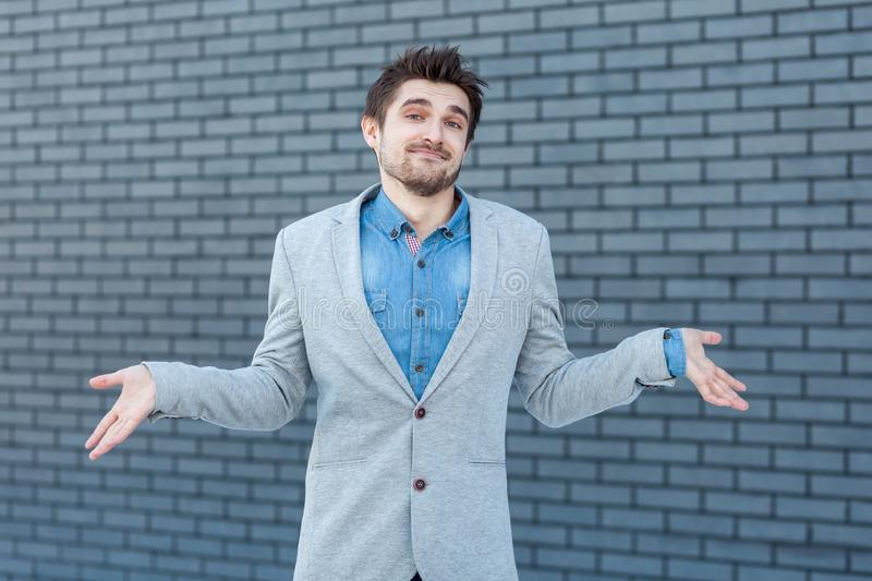 I don`t know. Portrait of confused handsome bearded man in casual style standing, raised arms and looking at camera with doubtful stock images