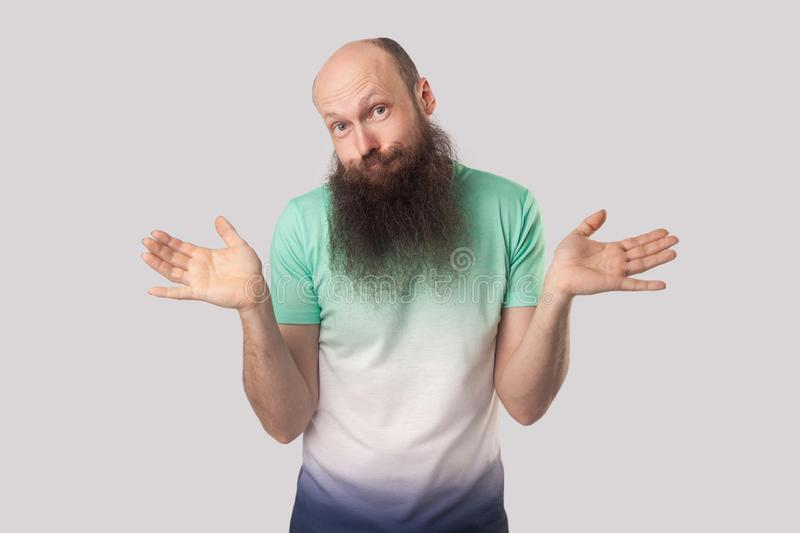 I don`t know. Portrait of puzzled or confused middle aged bald man with long beard standing with raised arms and looking at camer. A with doubtful face. indoor royalty free stock image