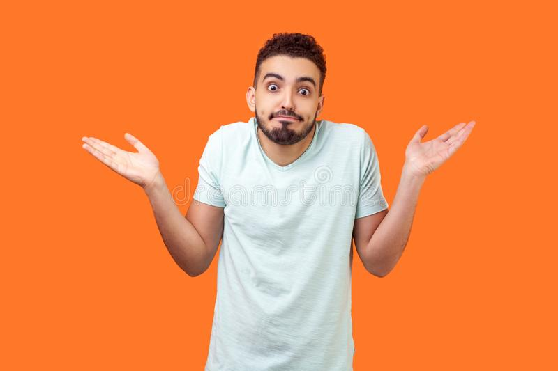 I don`t know, who cares. Portrait of confused clueless brunette man making no idea gesture. isolated on orange background stock image
