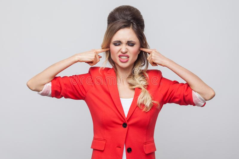 I don`t want to hear. Nervous business lady with hairstyle and makeup in red fancy blazer, standing clenching teeth and puting. Finger in ears. indoor studio royalty free stock images