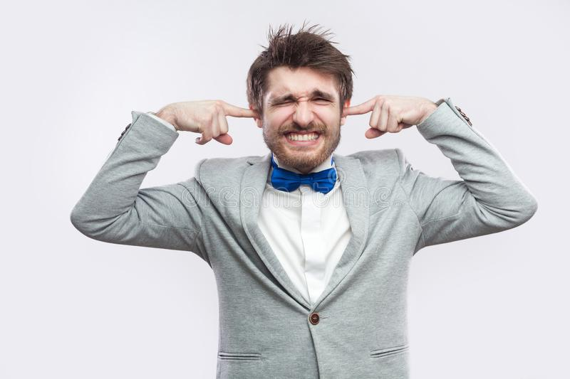I don`t want to hear. Portrait of worried handsome bearded man in casual grey suit, blue bow tie standing with closed eyes and stock photo