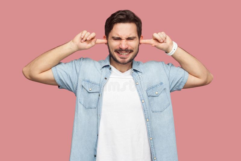 I don`t want to hear you. Portrait of confused handsome bearded young man in blue casual style shirt standing and putting fingers stock image