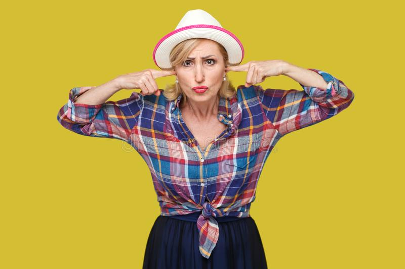 I don`t want to hear you. Portrait of serious modern stylish mature woman in casual style with white hat standing, putting finger stock photos