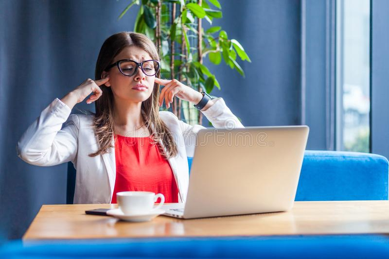 I don`t want to hear you! Portrait of young woman in glasses sitting, looking at her laptop screen on video call with finger royalty free stock images