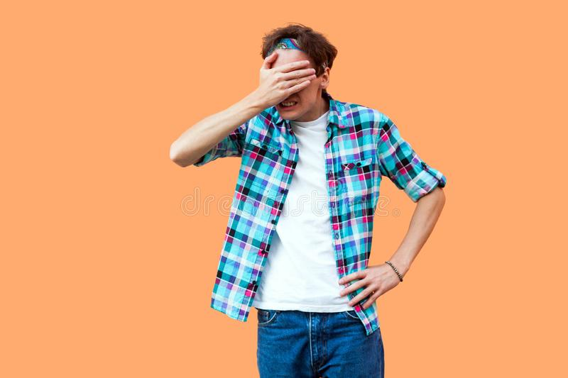 I don`t want to look at this. Portrait of shocked young man in casual blue checkered shirt headband standing, covering his eyes stock photography