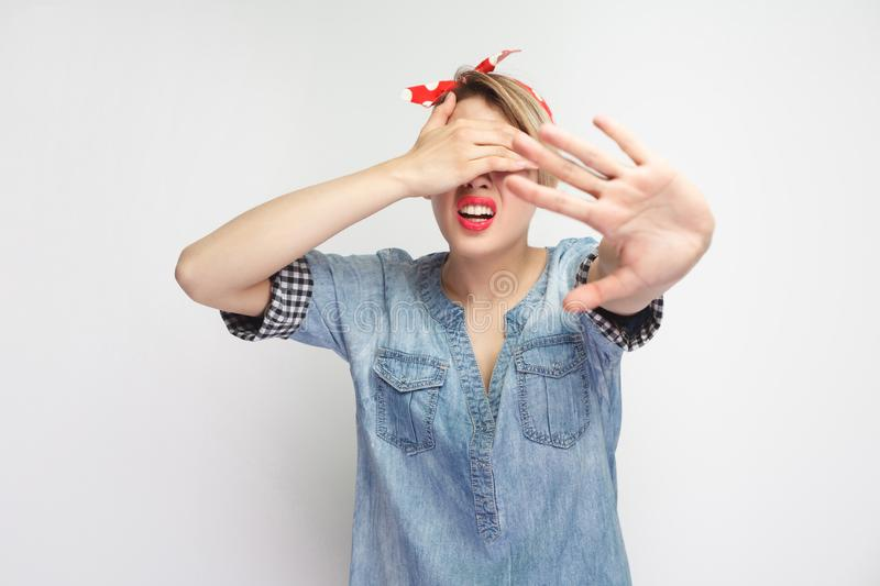 I don`t want to see this. Portrait of scared young woman in casual blue denim shirt and red headband standing, covering her eyes stock photos