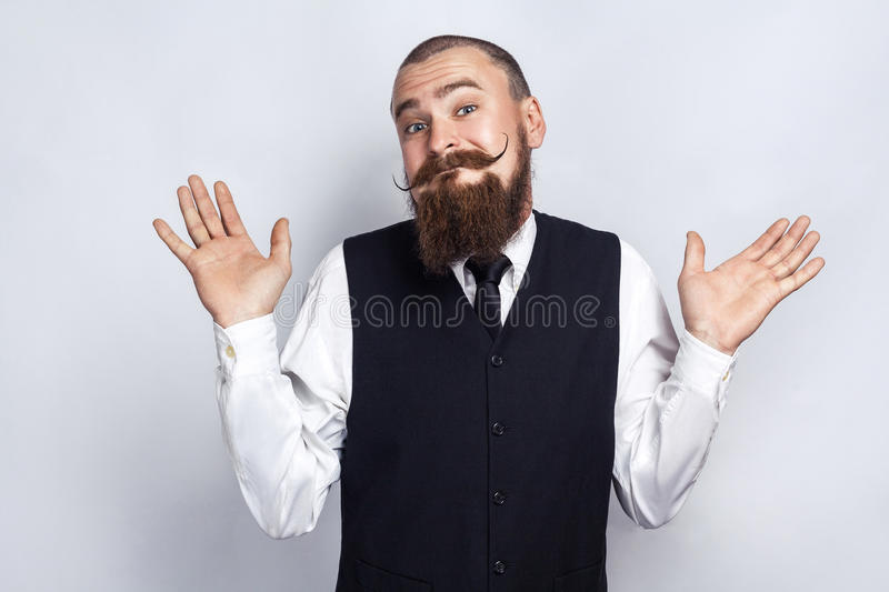 I Dont Know. Handsome businessman with beard and handlebar mustache looking at camera and confused. royalty free stock photo