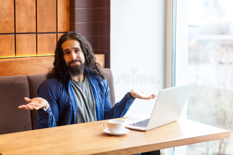 I dont know!Portrait of confused handsome young adult man freelancer in casual style sitting in cafe with laptop, raised hands and stock photos