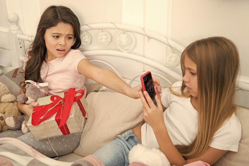 I dont like it. Small girls use phone in bed. Taking Christmas and New Year photo with smartphone. Happy small children. With mobile phone. Merry Christmas and stock photo