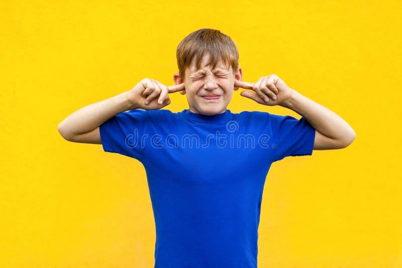 I dont want hear you! Sadness ginger boy holding fingers on ea stock image