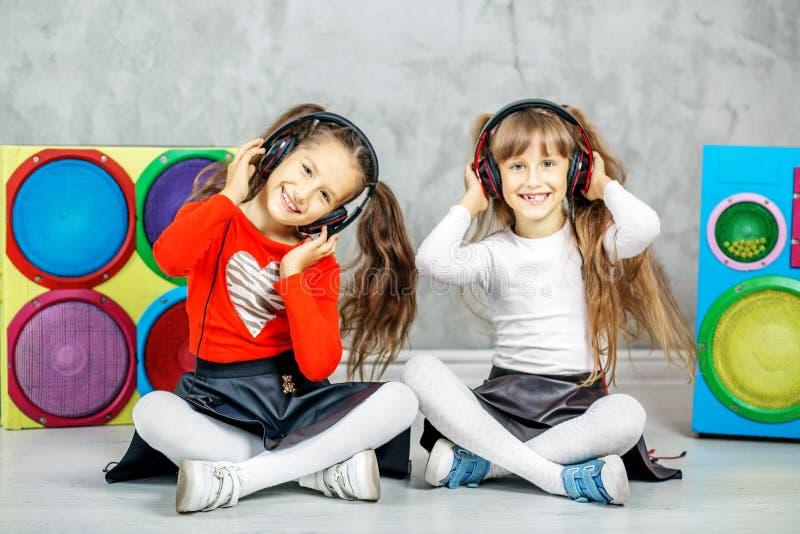 I due bambini ridono ed ascoltano le canzoni nelle cuffie immagini stock
