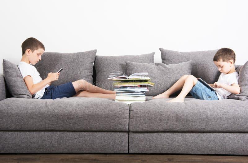 I due fratelli si siede nel lato opposto del sofà e considera i computer della compressa fotografie stock libere da diritti
