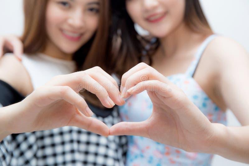 I due gemelli della donna che mostrano il cuore modellano con il primo piano delle mani immagine stock