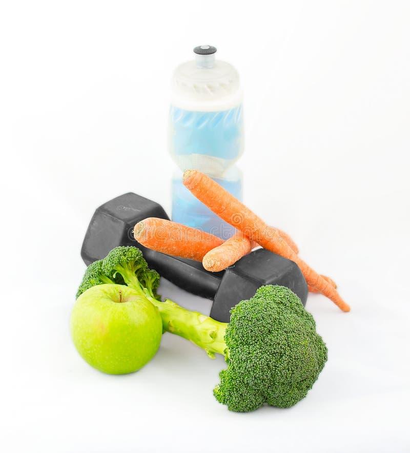 I Dumbbells fatti di broccolo con la bottiglia di acqua, carote e si inverdicono la a fotografia stock libera da diritti