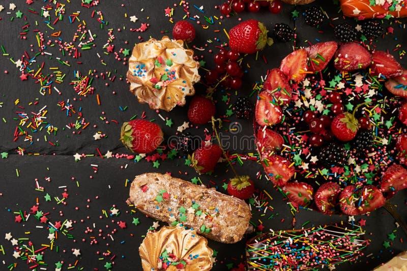 I eclairs e la bacca colourful deliziosi freschi dell'estate agglutinano con le bacche fotografia stock