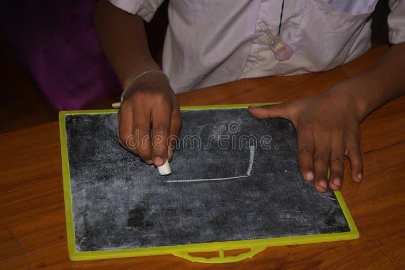 I en grundskola för barn mellan 5 och 11 år dras en bild på kritiserar med krita arkivbilder