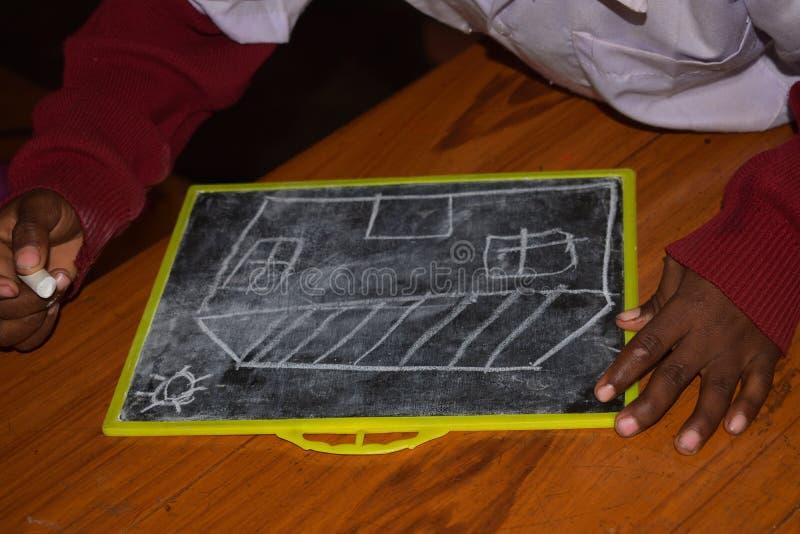 I en grundskola för barn mellan 5 och 11 år dras en bild på kritiserar med krita arkivfoton
