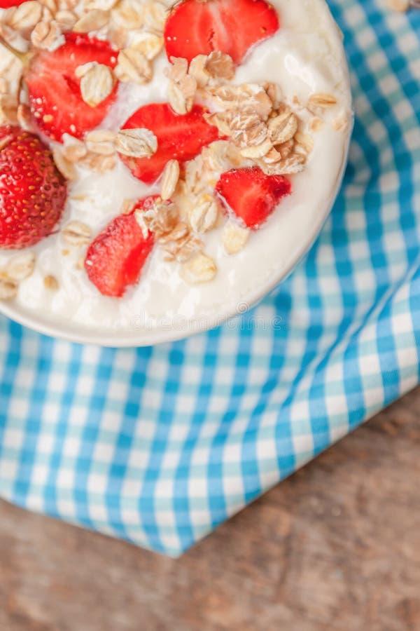 I en kopp av yoghurt, havregranola och nya jordgubbar på ett blått fotografering för bildbyråer