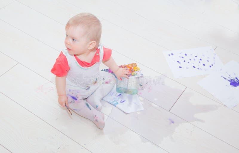 I en pöl av vatten sitter dolt i målarfärg av ett barn royaltyfri bild