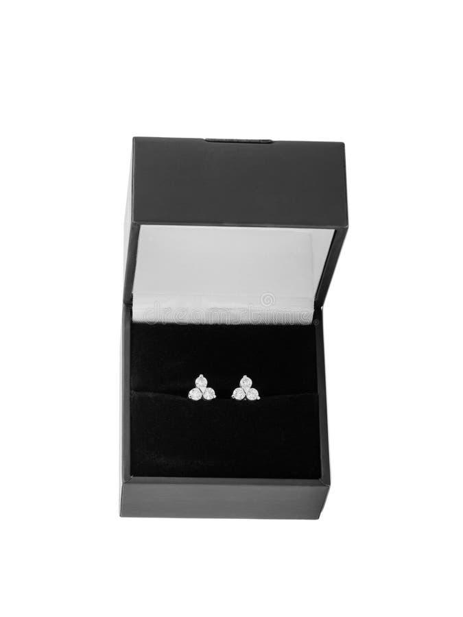 I en svart gåvaask är ett par av silverörhängen med ädelstenar Isolerat på vit Närbild royaltyfri fotografi