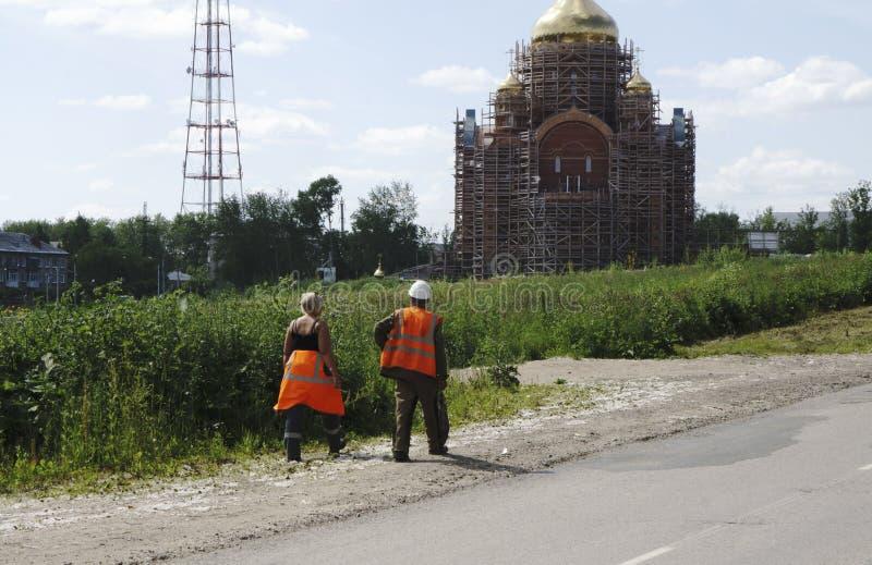 I en vithjälm är arbetare i orange overaller tillbaka från lunch fotografering för bildbyråer