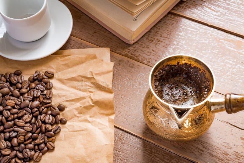 I fagioli arrostiti freschi del coffe in caffettiera turca tradizionale del cezve hanno aperto il libro e la tazza sulla tavola d immagine stock libera da diritti