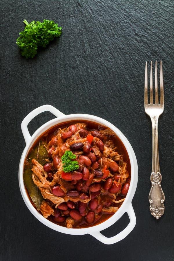 I fagioli con carne di maiale hanno stufato in salsa al pomodoro piccante con la cipolla, la paprica, la birra, la campana ed il  fotografia stock libera da diritti