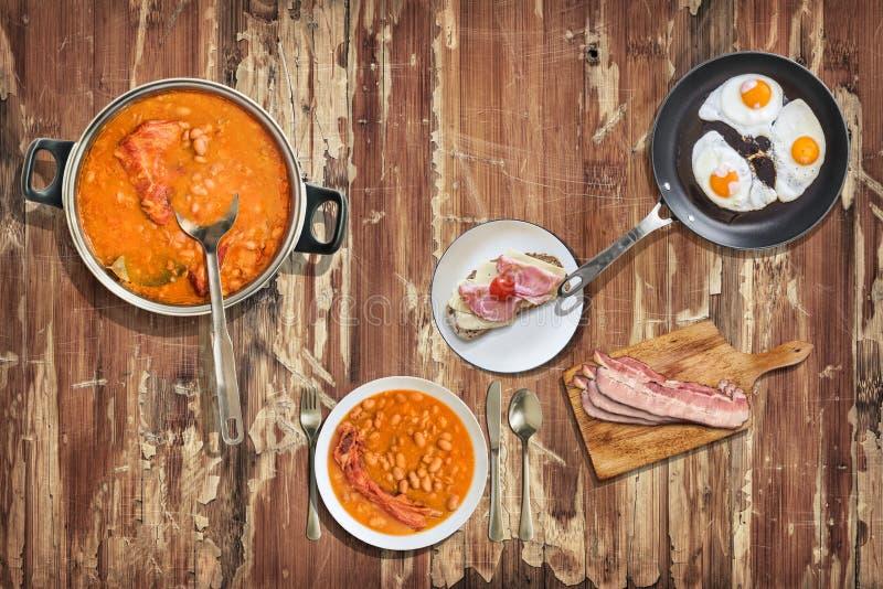 I fagioli in salsa con le costole di carne di maiale affumicate sono servito con le fette di lardo del bacon delle uova fritte ed immagini stock