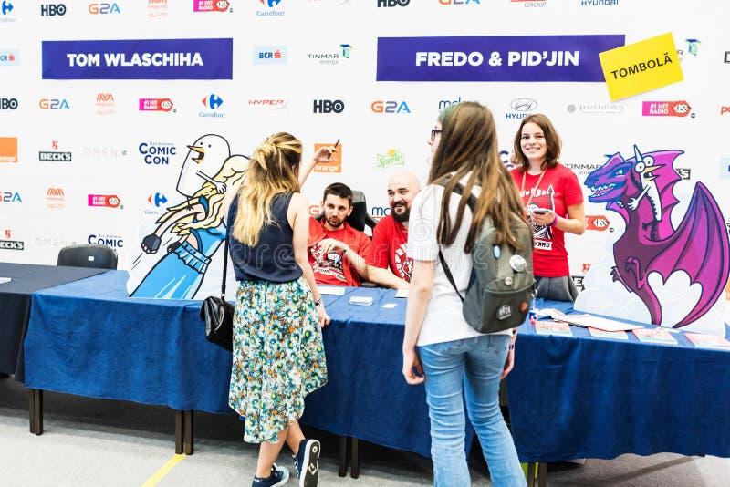 I fan che discutono e che prendono i libri hanno firmato da Fredo e da pidgin fotografia stock libera da diritti