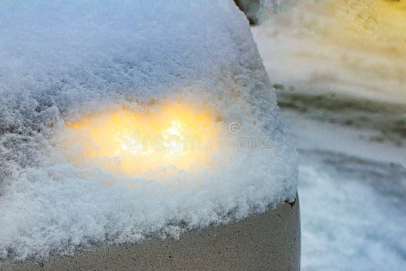 I fari leggeri capi d'ardore dell'automobile con uno strato di neve sono caduto dal cielo fotografie stock libere da diritti
