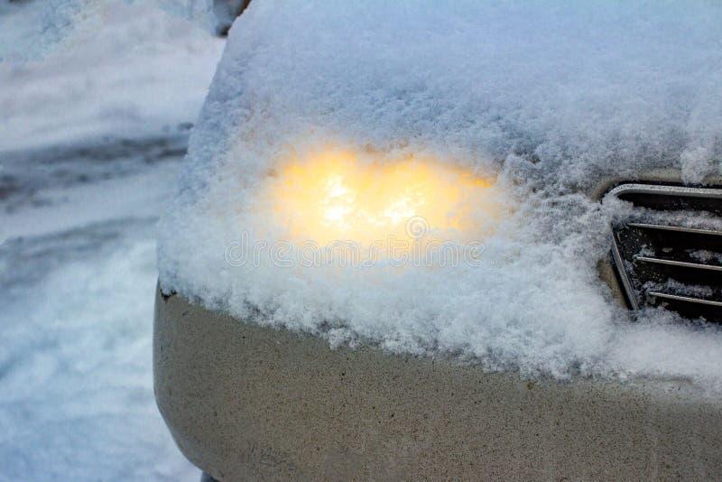 I fari leggeri capi d'ardore dell'automobile con uno strato di neve sono caduto dal cielo immagini stock libere da diritti
