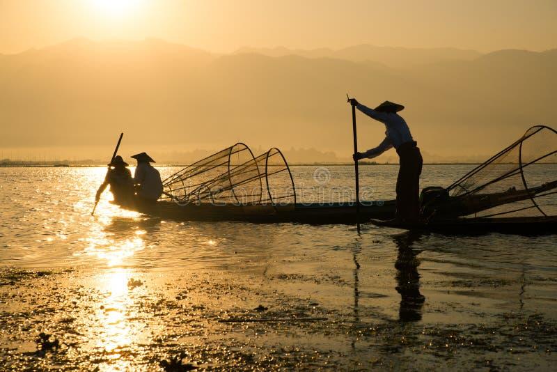 I fermi dei pescatori pescano per alimento nell'alba nel lago Inle immagini stock