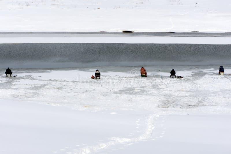 I fermi entusiasta del pescatore pescano nell'inverno nel foro fatto nel ghiaccio che copre il letto di fiume Accanto alla colata immagini stock libere da diritti