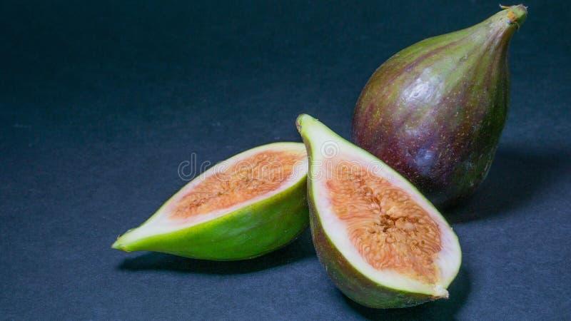 I fichi verdi, una frutta tagliano a metà due ed è un'intera frutta su un fondo luminoso scuro, primo piano fotografie stock libere da diritti