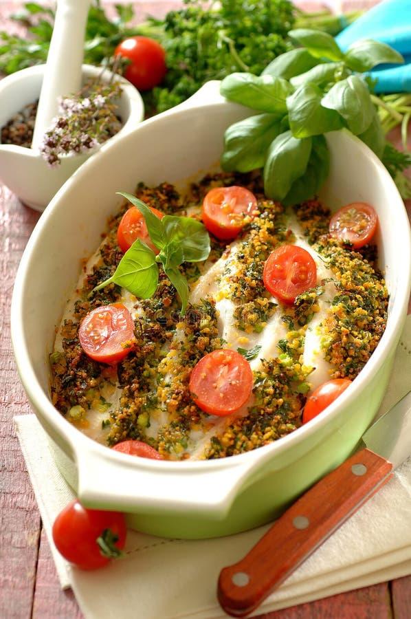 I filetti di pesce al forno hanno completato con la cipolla e le erbe fritte croccanti fotografia stock libera da diritti