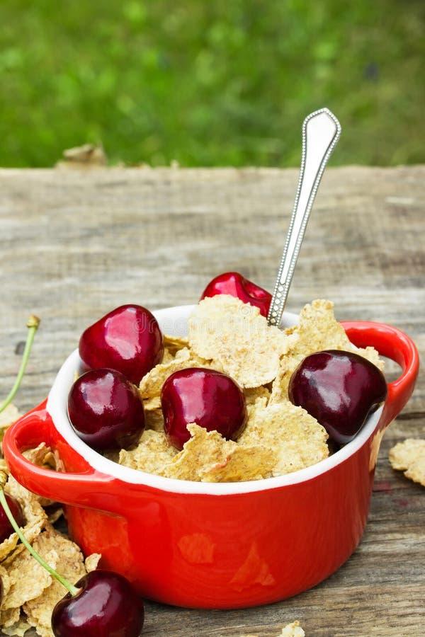 I fiocchi di frumento con la ciliegia collegano in un vaso ceramico fotografie stock