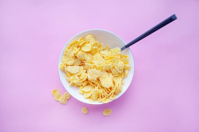 I fiocchi di granturco asciugano la prima colazione in un piatto bianco con un cucchiaio su un backgroud rosa Vista superiore fotografia stock libera da diritti