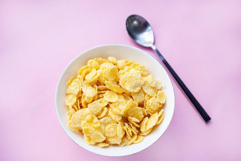 I fiocchi di granturco asciugano la prima colazione in una ciotola bianca con un cucchiaio su un backgroud rosa fotografia stock libera da diritti