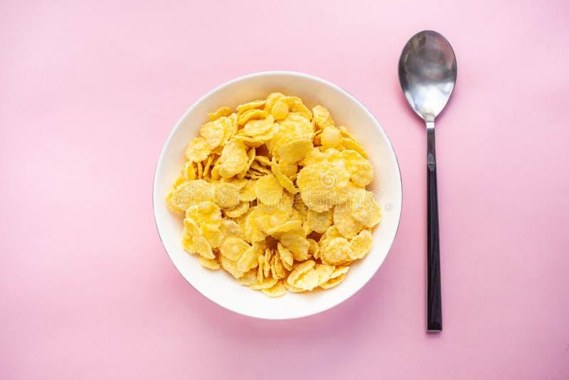 I fiocchi di granturco asciugano la prima colazione in una ciotola bianca con un cucchiaio su un backgroud rosa Vista superiore fotografia stock libera da diritti