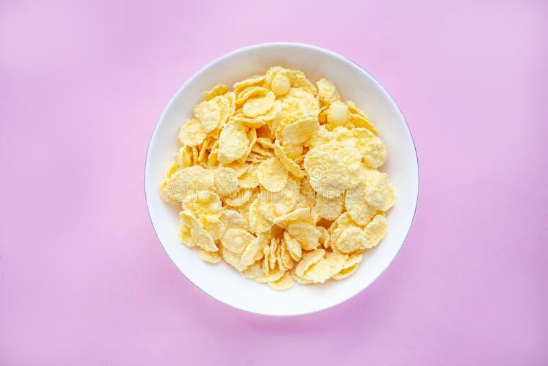I fiocchi di granturco asciugano la prima colazione in una ciotola bianca su un backgroud rosa Vista superiore immagine stock libera da diritti