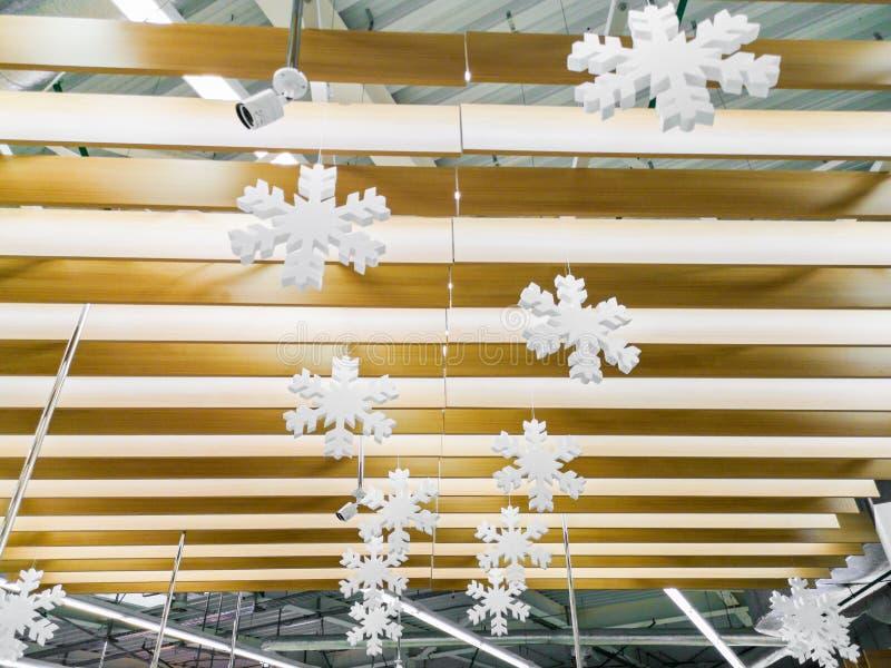 I fiocchi di neve appendono su un albero, fiocchi di neve appendono sul soffitto Natale fondo lunatico interno, interno di Natale fotografia stock libera da diritti