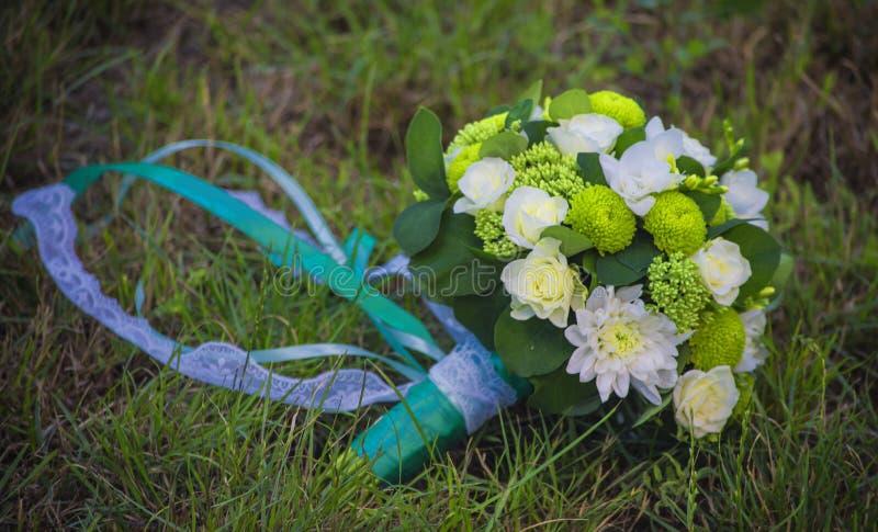 I fiori bianchi in un mazzo della sposa sono legati con i nastri fotografia stock libera da diritti