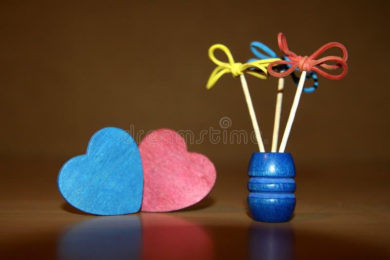 I fiori creativi di gomma e degli stuzzicadenti rossi ed il cuore di legno blu hanno modellato i cuori fotografia stock libera da diritti