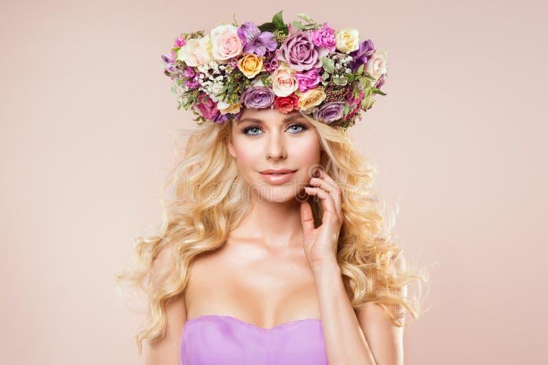 I fiori dei modelli di moda avvolgono il ritratto di bellezza, trucco di nudo della donna con Rose Flower nell'acconciatura, bell immagine stock libera da diritti