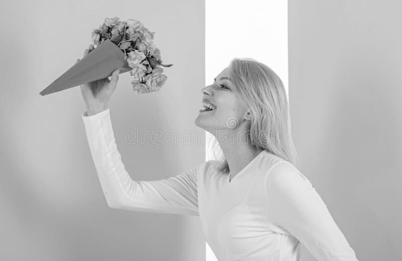 I fiori del mazzo della tenuta della ragazza godono della fragranza favorita Fiori favoriti ricevuti felici di signora come regal fotografia stock