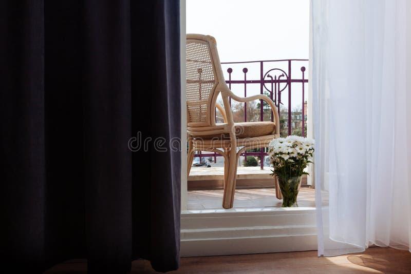 I fiori della tavola del terrazzo osservano il vimine della via del sole dei fiori della sedia del balcone di legno fotografia stock