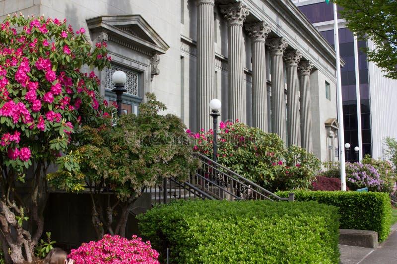 I fiori ed il cielo blu circondano una costruzione di governo in Washington State immagine stock libera da diritti