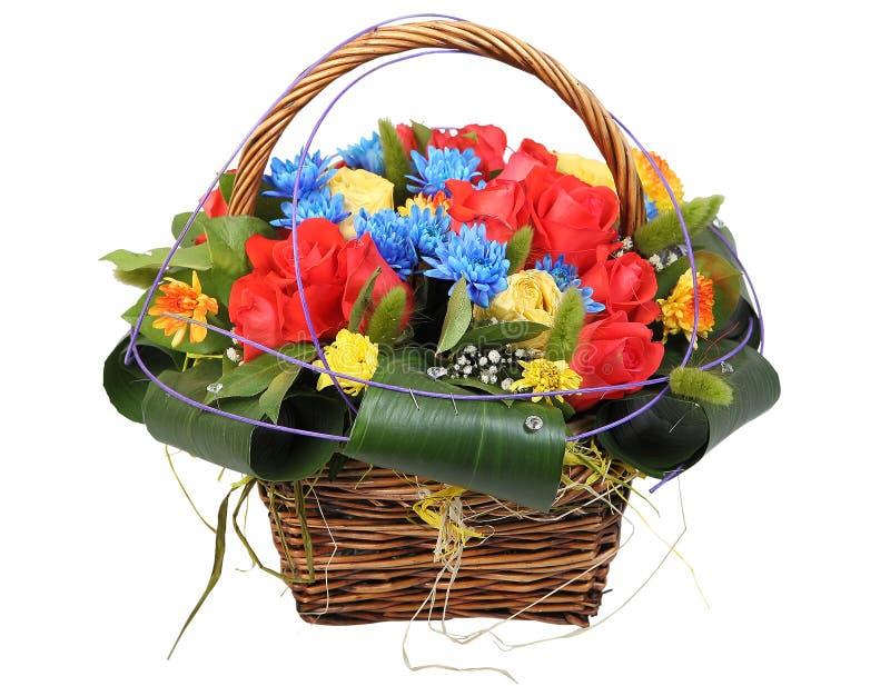 I fiori legano il canestro di vimini, con le rose rosse e il chrysanthe blu immagine stock