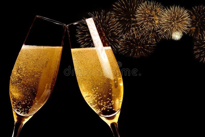 I flûte con le bolle dorate fanno l'acclamazioni con i fuochi d'artificio scintillare ed annerire il fondo fotografia stock libera da diritti