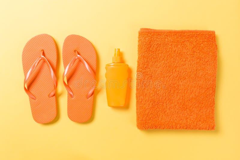 I Flip-flop arancio con l'asciugamano sul piano giallo di vista superiore del fondo pongono con lo spazio della copia Concetto di fotografie stock